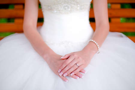 happy bride showing hands and jewlery on wedding dress on wedding day  photo