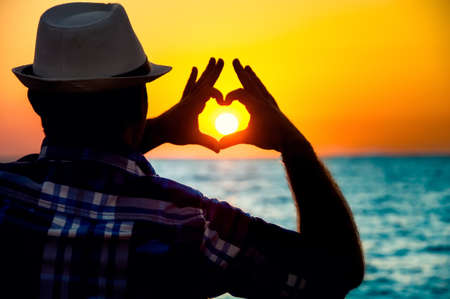 sihlouette: silhouette of a Man showing love  with fingers in the sunset on beach Stock Photo