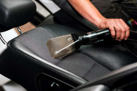 Auto car service cleaning the drivers seat, clealing and vacuuming leather photo