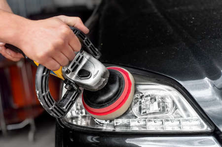 burnish: Car headlights cleaning with power buffer machine at car service