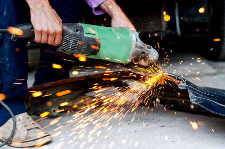 power tools: Professional factory worker cutting metal with grinder and generating sparks Stock Photo