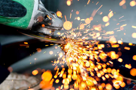 Professional welder, worker cutting metal with grinder generating sparks