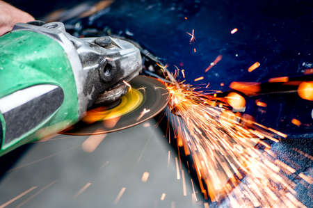 Heavy industry worker cutting steel with angle grinder in workshop, at car service