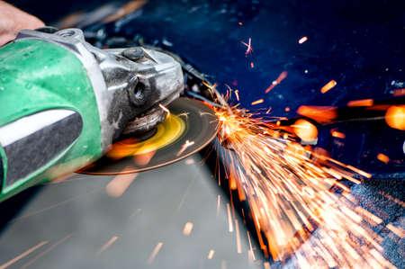 molinillo: Trabajador de la industria pesada de corte de acero con la amoladora angular en el taller, en el servicio de coche