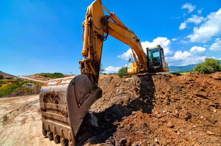 Yellow excavator moving soil and sand  on road construction site photo