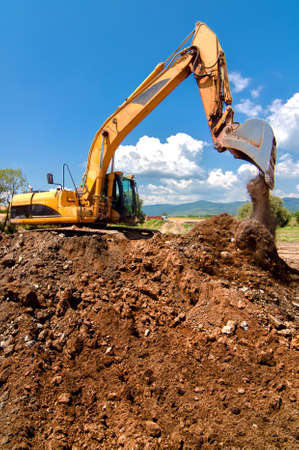 Yellow heavy duty industrial excavator working and loading sand into dumper truck Stock Photo - 21727779