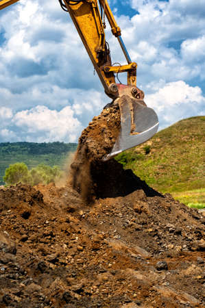 open cast mine: Heavy duty vehicule scoop working with soil and sand on construction site