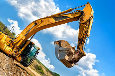 heavy duty, industrial excavator moving soil and sand on road construction site photo