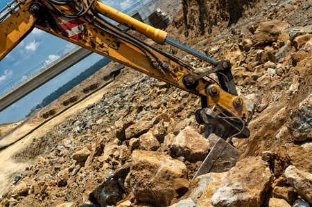 Excavator engineer moving sand and rocks with heavy duty scoop photo