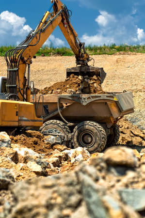 Excavator loading heavy duty dumper truck with rocks on construction site photo