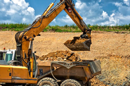 Professional construction worker with excavator loading rocks into a dumper truck Stock Photo - 21727854