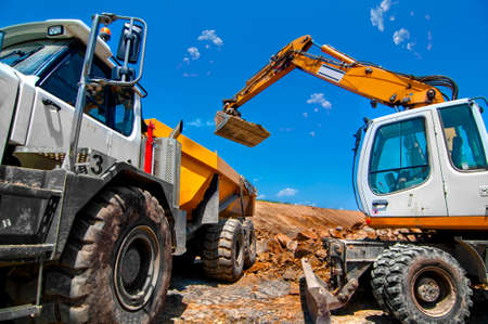 Big, industrial excavator on new construction site loading a dumper truck, in the background the blue sky and sun photo