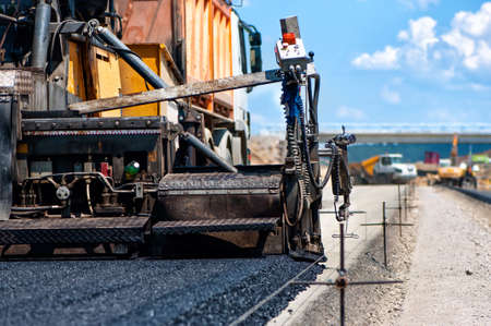 asphalting: pavement machine laying fresh asphalt or bitumen on top of the gravel base during highway construction