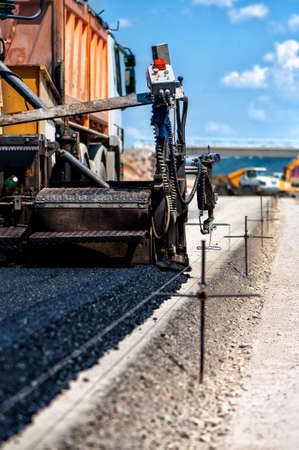 multilayered: Industrial pavement truck or machine laying fresh bitumen and asphalt on base of a highway construction
