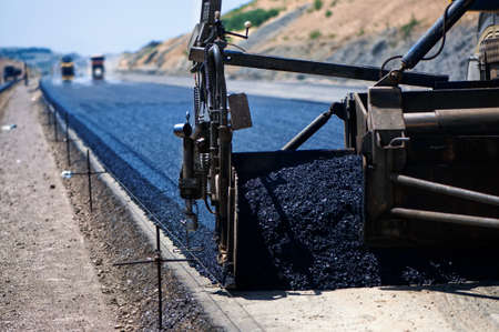 asphalt paving: industrial pavement truck laying fresh asphalt on construction site