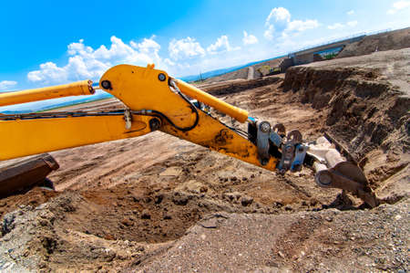 Industrial excavator moving earth and loading a dumper truck on road construction site photo