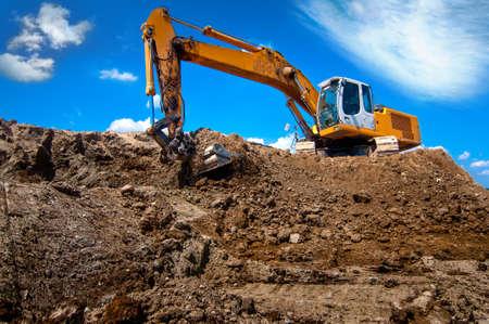 industrial excavator loading soil from sandpit into a dumper truck