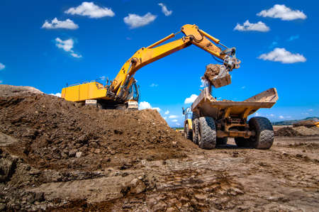 industrial excavator loading soil from sandpit into a dumper truck photo