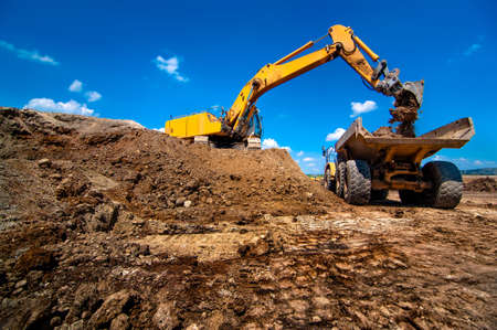 heavy: Industrial excavator loading soil material from highway construction site into a dumper truck Stock Photo