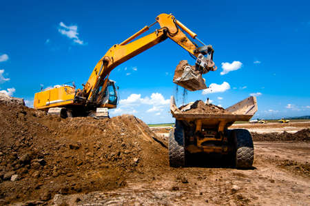 equipment: Industrial truck loader excavator moving earth and unloading into a dumper truck