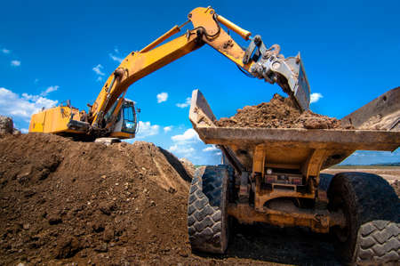 Yellow excavator loading soil  into a dumper truck on construction site photo