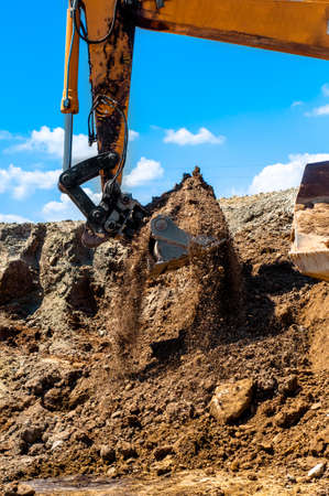 heavy duty excavator scooping sand and loading dumper trucks photo