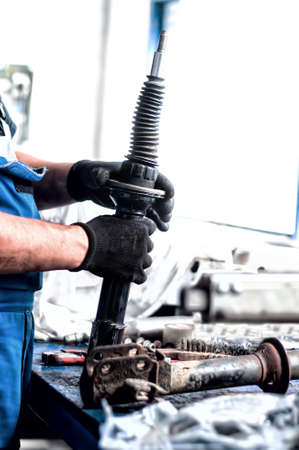 Auto engineer mechanic working on car shock absorber in car service workshop Stock Photo - 21728042