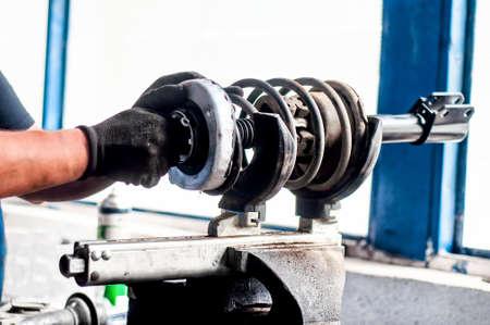 車サービスのワーク ショップでの車のショックアブソーバーを調整する自動機械エンジニア