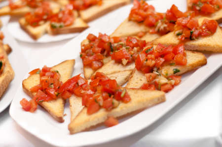 Juicy tomatoes on fresh bread, pesto as topping  Italian antipasto called bruschetta photo
