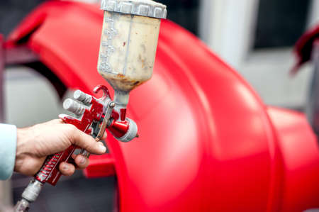car garage: Close-up of spray gun with red paint painting a car in special booth