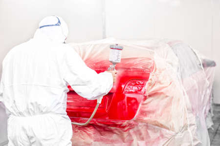 Auto mechanic painting with airbrush a red car in special booth