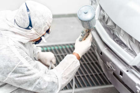 bodywork: auto mechanic engineer painting a grey car in a special booth