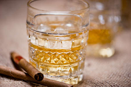 Close-up of whiskey glass on the rocks with cigars  photo