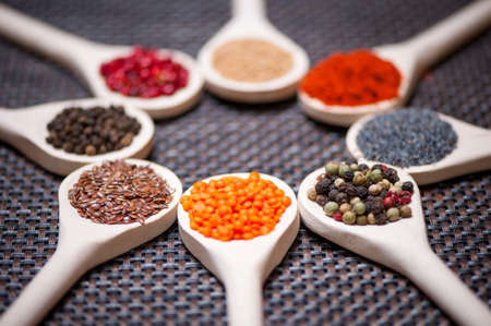 groat: Various kind of spices on wooden spoon -  detail of bean seeds