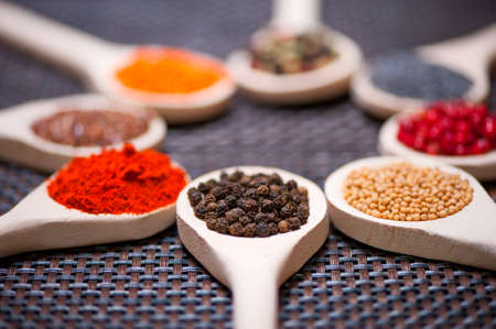Various kind of spices on wooden spoon -  detail of black pepper seeds photo