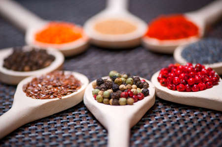 cilantro: Diversos tipos de especias en la cuchara de madera - el detalle de las semillas de pimienta negra, verde y roja Foto de archivo