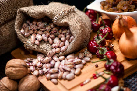 Bio onions, nuts, beans and dried pepper as food ingredients on kitchen table photo
