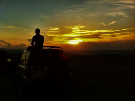 man: Silhouette of a young man sitting on top of a wheel drive car Stock Photo