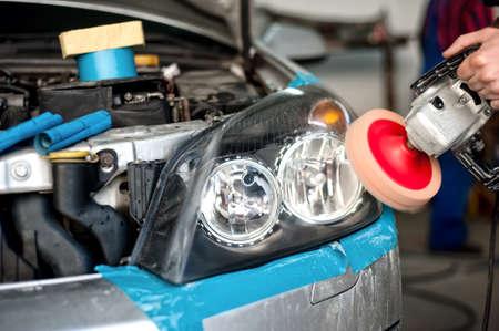 car polish: auto mechanic working on polishing a car headlight with power buffer machine in car care system