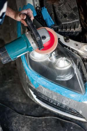 buffing: mechanic cleaning headlights with polishing power buffer machine Stock Photo