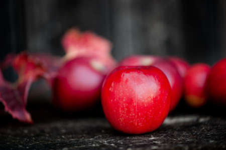 Organic red apples from autumn harvest in agriculture theme against wooden background photo