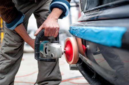 professional mechanic using a power buffer machine for cleaning the body of a car from scratches. Detail of car care concept Stock Photo - 23327568