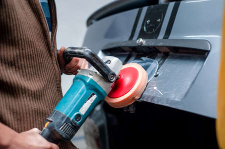 buffing: professional mechanic cleaning the metal surface of the bodywork of a car with power buffer machine. Polish procedure and car care concept Stock Photo