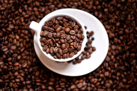 fresh black columbian coffee in white cup isolated on coffee beans background photo