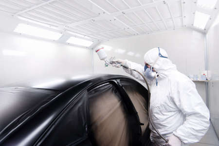 isolated on gray: Automotive mechanical engineer painting the body of a black car with special suit