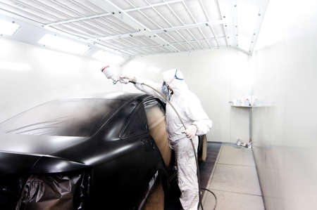bodywork: Automotive industry - engineer painting and working on a black body of a car and wearing protective gear Stock Photo