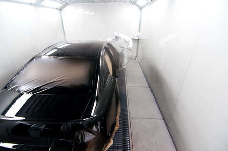 worker painting a blacck car in a special booth wearing protection gear