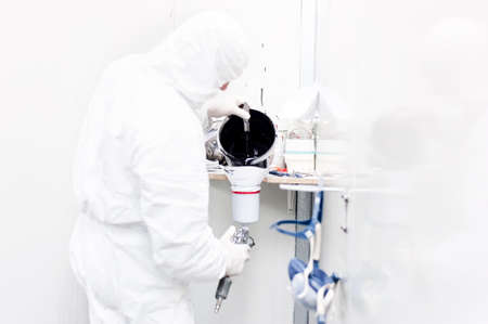 Auto worker preparing black paint for body work on a car wearing white special suit Фото со стока