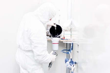 body paint: Trabajador Auto prepara la pintura negro para el trabajo del cuerpo en un coche que llevaba traje especial blanco