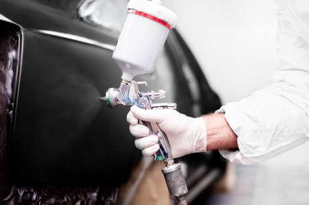 body paint: Trabajador que usa una pistola de pintura para pintar un coche Foto de archivo